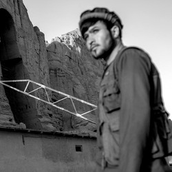A member of the Taliban stands guard in front of a building with a Taliban flag.