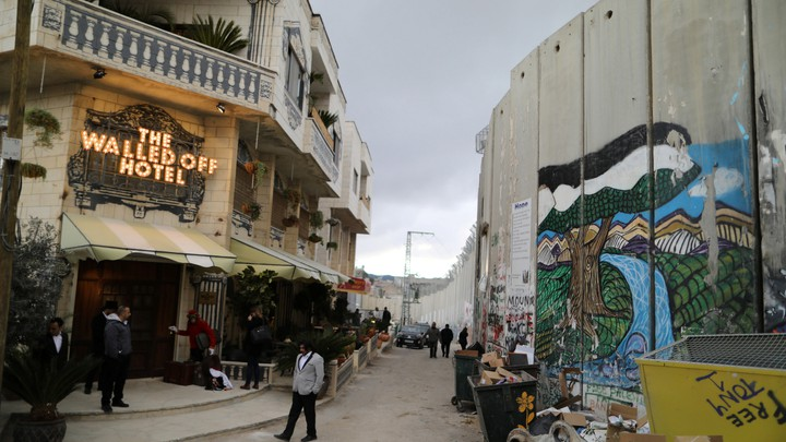 People stand outside the Walled Off hotel, which was opened by street artist Banksy, in the West Bank city of Bethlehem.