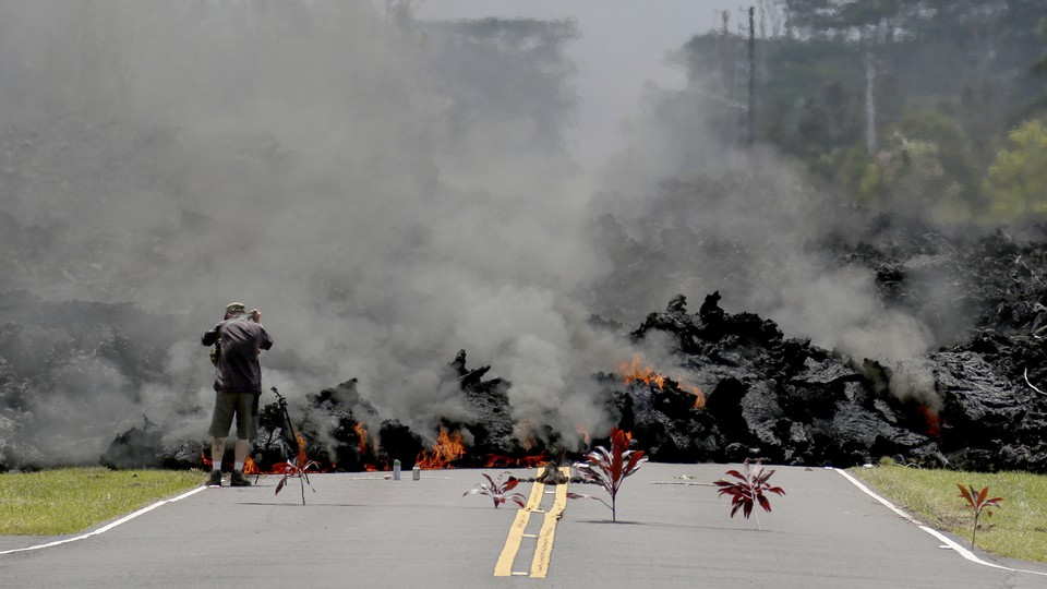 Bundles of leaves lie along a road where lava is moving toward them.
