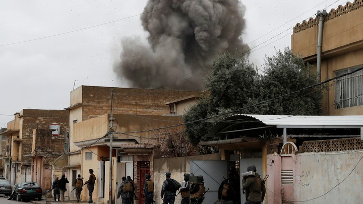 Iraqi policemen walk during an airstrike against Islamic State militants in Mosul, Iraq, on March 4, 2017.