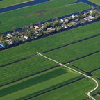 Aerial view of narrow strips of land divided by water, some with houses on them.