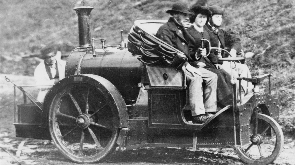 Three people riding in an 1860s Rickets steam carriage.