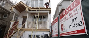 A man works on the roof of a house with a for sale sign next to it.