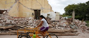 A woman on a bicycle drives pass a house destroyed by the earthquake that struck the southern coast of Mexico late on Thursday, in Ixtaltepec, Mexico.