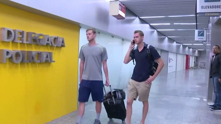 U.S. Olympic swimmers Gunnar Bentz and Jack Conger walk Wednesday to the airport police station office at Rio's international airport.
