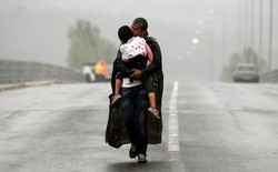 A Syrian refugee carries his daughter in Greece as he approaches the Greek-Macedonian border in September 2015.