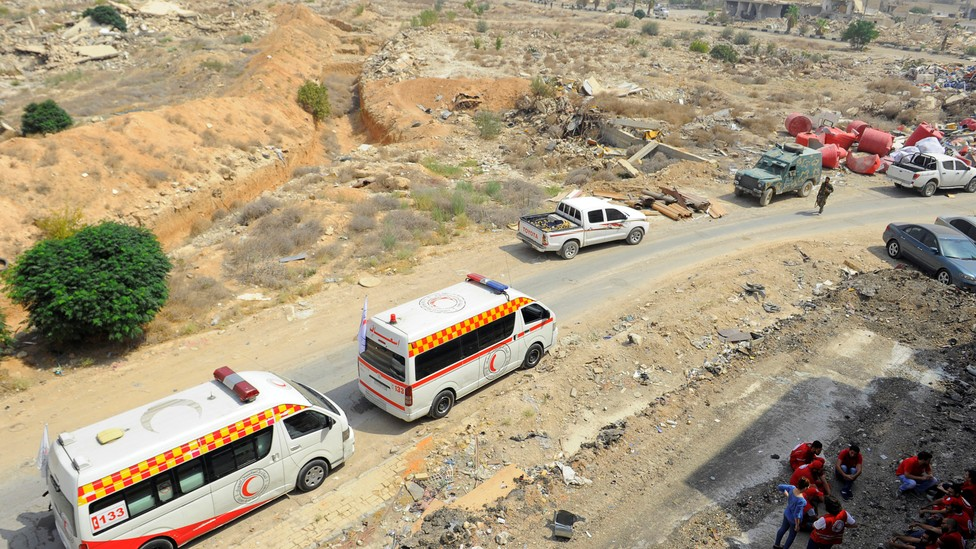 A Syrian Arab Red Crescent convoy waits at the entrance of the besieged Damascus suburb of Daraya on August 26, 2016.