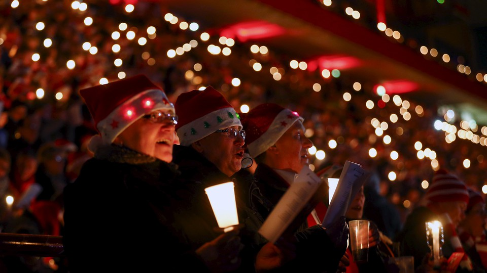 Christmas carolers wear Santa Claus hats