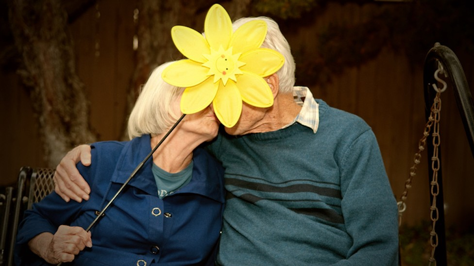 An older couple is kissing, and the woman is holding up a large yellow plastic lawn flower to hide their faces.