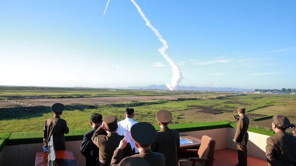 North Korean leader Kim Jong Un watches the test of a new-type anti-aircraft guided weapon system.
