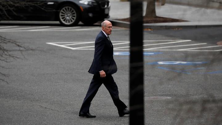 A long shot of Dan Coats walking through an empty parking lot.