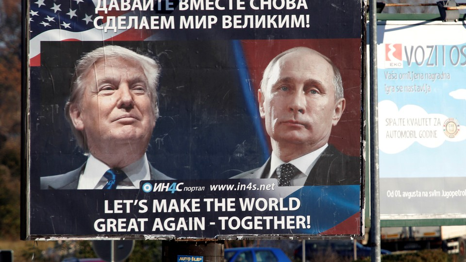 Pedestrians cross the street behind a billboard showing a pictures of President Trump and Russian President Vladimir Putin.