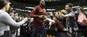 LeBron James enters an arena as fans snap photos and reach out to touch him.