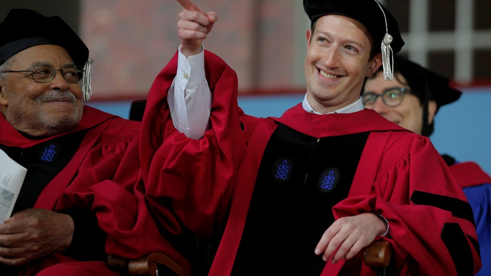 The Facebook founder Mark Zuckerberg points and smiles while wearing a cap at gown at Harvard's commencement