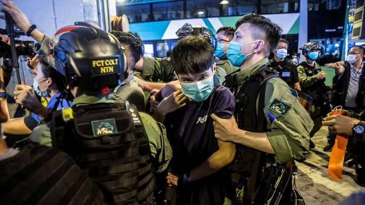 A riot police officer detains a man during a protest outside a Hong Kong shopping mall.