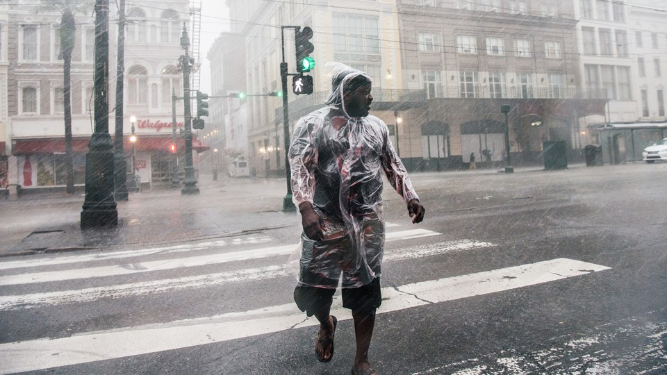 A person crosses a street in New Orleans under heavy rainfall during Hurricane Ida.