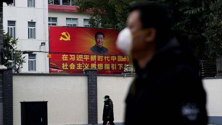People wearing masks walk past a portrait of Chinese President Xi Jinping.