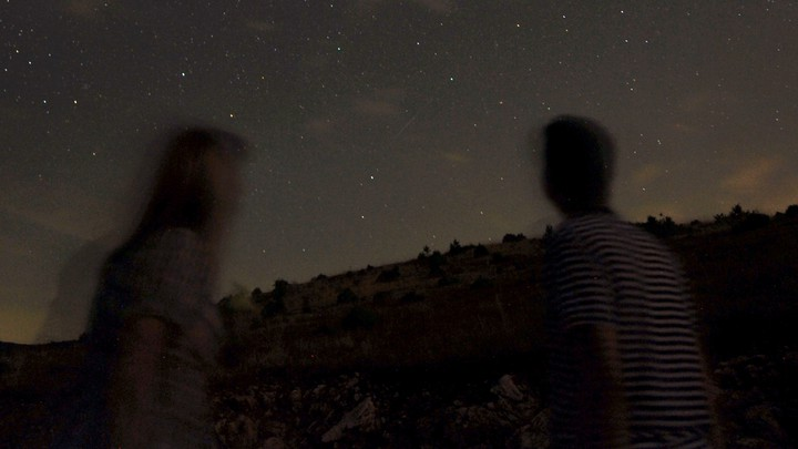 Two blurry figures look at the stars.
