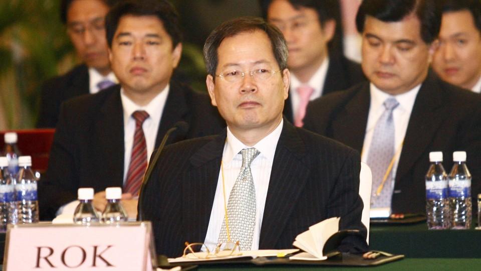 Chun Yung Woo sitting at a lectern
