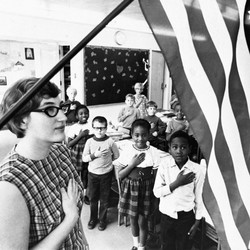 An archival photo of an American classroom saluting the American flag