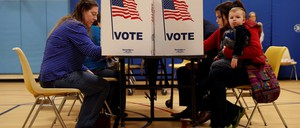 People are pictured at voting booths.