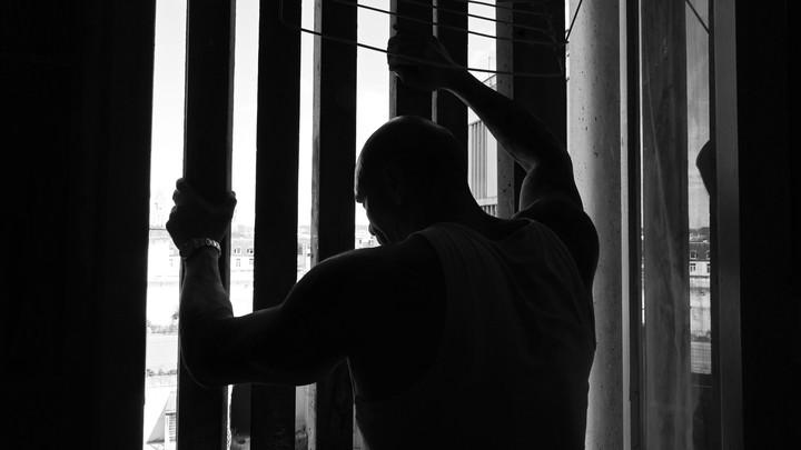 prisoner holding onto bars