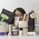 The writer's face, partially obscured by a pile of Goop products