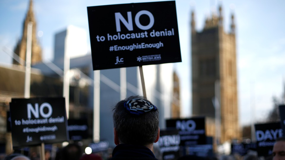 Protesters hold placards and flags during a demonstration against anti-Semitism in Parliament Square in London on March 26, 2018.