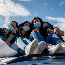 Four graduating high-school students wearing face masks.
