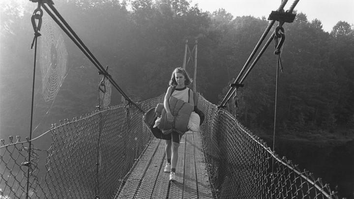 A girl carrying a sleeping bag walking over bridge