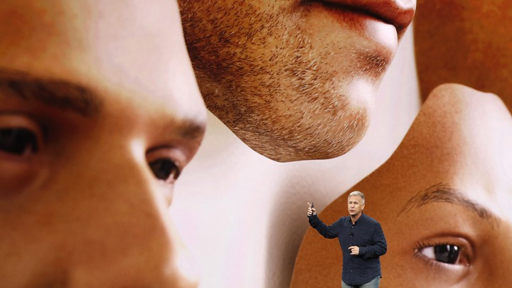 Phil Schiller stands in front of a screen displaying images of disembodied faces.