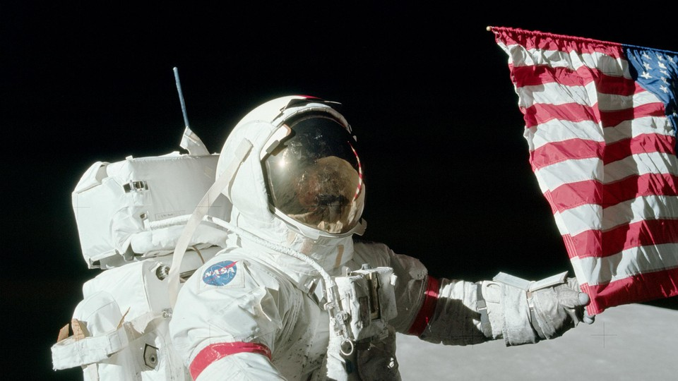 Gene Cernan holds the American flag during a spacewalk on the Apollo 17 mission on December 12, 1972.