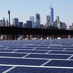 A rooftop is covered with solar panels at the Brooklyn Navy Yard in New York, with the Manhattan skyline in the distance.