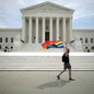 A person flies a pride rainbow flag outside the Supreme Court