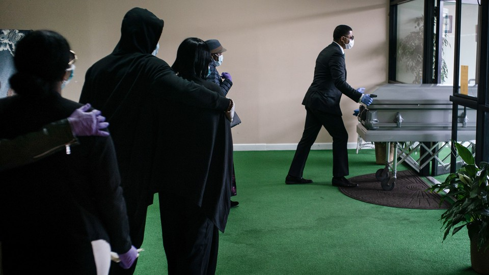 A funeral procession in New Jersey. A black man wearing a mask is pushing a casket.