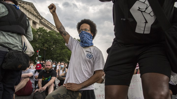 A demonstrator in D.C. raises a fist while protesting against police brutality and racism. This is the 12th day of protests with thousands of people descending on the city to peacefully demonstrate in the wake of the death of George Floyd, an African-American man who was killed in police custody in Minneapolis on May 25. (Photo by Probal Rashid / LightRocket via Getty)