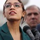 Alexandria Ocasio-Cortez stands at a bank of microphones in a green jacket.