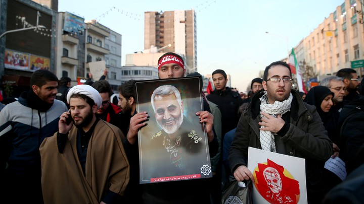 A man holds a photograph of Qassem Soleimani during the general's funeral procession while walking next to others.