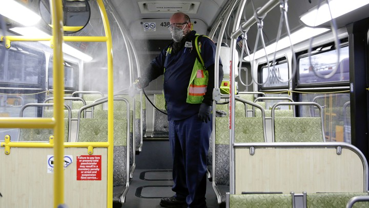 A King County Metro equipment service worker sanitizes a bus.