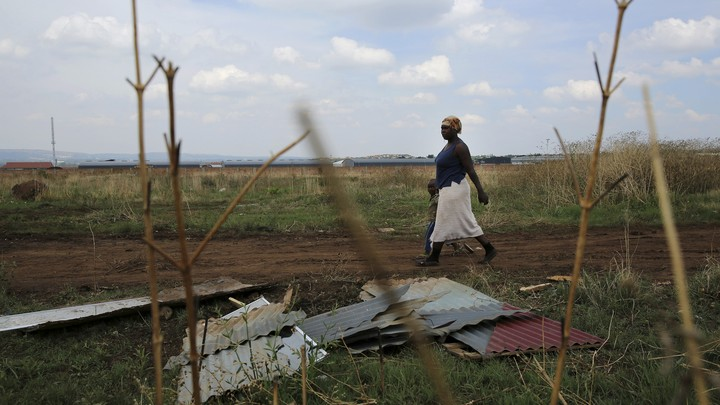 A mother and child walk past corrugated iron left by residents who intended to build an informal settlement.