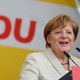 German Chancellor Angela Merkel gives a speech with her party's sign in the background.