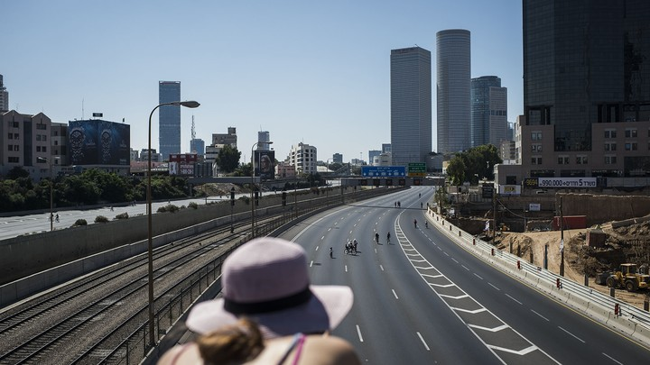 People ride their bicycles in the middle of the empty streets of Tel Aviv during Yom Kippur on October 04, 2014 in Tel Aviv, Israel.