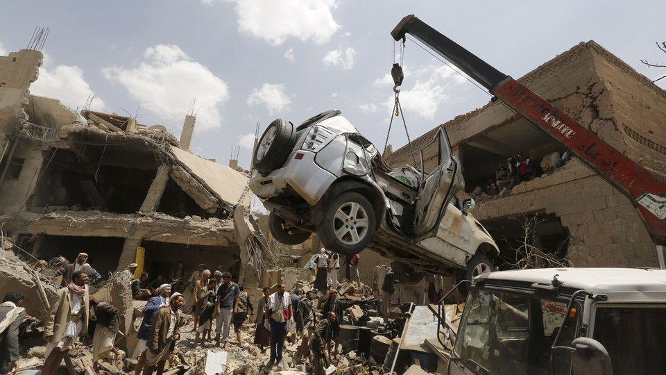 A car is lifted by a crane at the site of a Saudi-led air strike in Yemen's capital Sanaa.