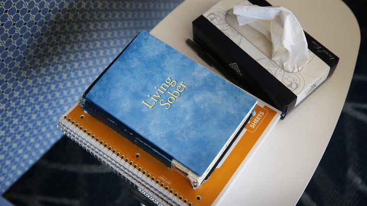 "A book titled ""Living Sober,"" spiral notebooks, and a tissue box on a table"