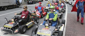 People dressed in costumes as Super Mario, super heroes and others drive custom built Go-Karts through a street in Tokyo.
