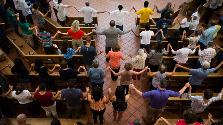 People stand and hold hands in a church.
