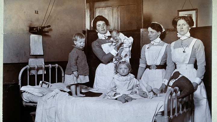 A black-and-white photograph of three women and three young children standing around a bed