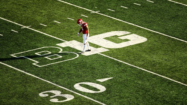A football player walking across a football field.