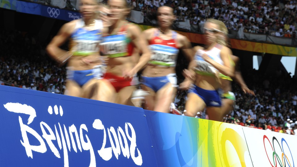 Runners appear blurry in this photo of competitors of a track event at the Beijing Olympics in 2008