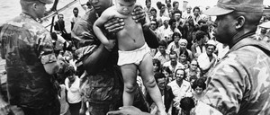 A U.S. Marine helps a young Cuban child off a refugee boat